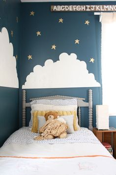big boy room: peacock walls, clouds, jenny Lind crib in chalk paint, vintage dresser painted white
