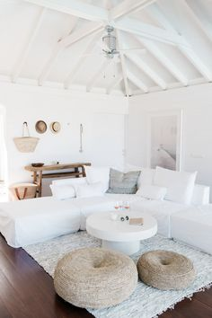 creamy white living room with touches of natural texture like the sitting poufs and wooden entry table // love the exposed beams painted white // home decorating // interior design