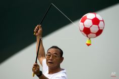In this Sunday, June 2015 photo, a man spins a top mount with an inflatable ball during a public sport campaign to promote exercise at Garden Expo Park in Beijing. The Allure, Soccer Ball, Beijing, June, Sunday, Public, Exercise, Digital, World