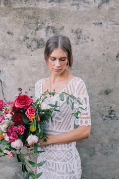 bride wearing geometric wedding dress by Stone Cold Fox with a wild and vibrant wedding bouquet