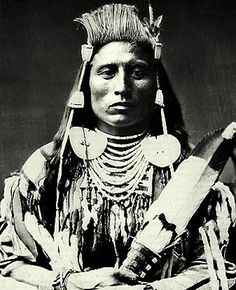 Medicine Crow - Perits Shinakpas (Crow) 1848-?; traditional Crow war chief, scout for US army and grandfather of WW2 veteran and Crow historian Joe Medicine Crow.  Note traditional Crow hair style.  Photo: 1880.