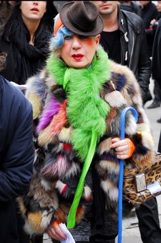 that lime green boa? stole? scarf? on top of the multicolored fur coat? cape? balances out the tiny hat and skinny cane