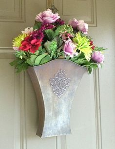 Front Door Greetings! - Debbie Reynolds Harper      I love my door-basket! At Christmas time, I filled it with a big bunch of poinsettias! And now that it's spring, I have a burst of colorful flowers arranged in a bouquet tucked down inside the nice detailed metal basket.