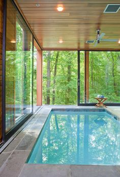 Indoor pool with reflective wooden ceiling, concealed lighting and air extraction, slate sides, huge windows and trees immediately outside.