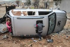 Syrian kids play in a destroyed car in center of the Syrian town of Kobani (Ayn al-Arab), Feb. 18, 2015. The town had just been freed from Islamic State forces.