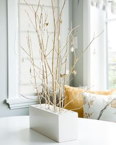 DIY holiday décor doesn't need to be complicated. When we decorated this sweet family home we simply painted some branches gold, lodged them into a vase using white pebbles and hung tiny ornaments for a whimsical centre piece on the kitchen table. #interiordesign #inspiration #decor #holiday #giving White Pebbles, Asian Design, Deck Design, Centre Pieces, Indoor Plants, Glass Vase, Home And Family, Interior Design, Holiday Decor