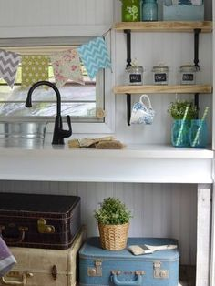 Funky kitchen--sink made from a bucket, suitcases for storage.