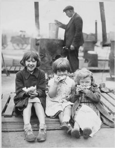 Three children eat American cheese sandwiches at an emergency feeding centre in Liverpool. Behind them, a man can be seen cooking at a Soyer boiler or field cooker. One girl is laughing as she eats. 1941.
