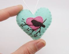 This little heart ornament was all hand stitched, embroidered, and appliqued using the teeniest pieces of felt and even teenier stitches in shades of mint green, dark pink, and brown.  It features a bird silhouette perched in a tree branch with a little heart backdrop. A tiny heart and the year 2017 are hand stamped on an aluminum tag that adorns the back of the ornament.  Lightly stuffed with poly-fill and finished with a loop of cotton cord for hanging. Perfect addition to a Valentines Day…