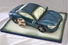 "Aston Martin Vanquish Cake - This was a car cake done for a 21st birthday. The cake is entirely edible save for two cocktail sticks holding the wing mirrors in place and was carved by hand from a 16"" long by 6/7"" deep by 8"" wide block."