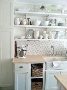 This crisp white cottage kitchen is both beautiful and functional. Open shelves display all-white dishes and vintage pieces. The bead board wall combined with the ceramic backsplash gives the space texture, form and function . The farmhouse sink is a standout feature against the neutral colored limestone countertops.