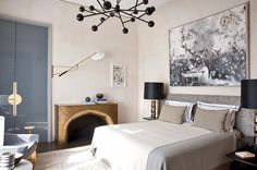 Sublime grey interior with beautiful wall art and a gorgeous golden fireplace and molecular sputnik chandeliers