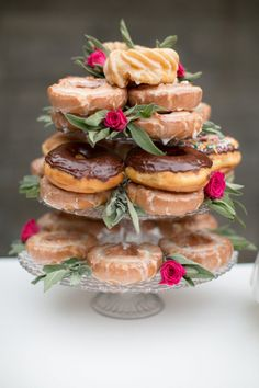 Donut tower idea - Boston creme, glazed and sprinkle donuts displayed on a three-tier glass tower with bright pink roses {Stephanie Fay Photography}