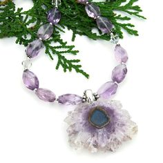 The EARTH FLOWER necklace is truly a stunning piece of handmade gemstone jewelry. The focal is a dazzling purple amethyst stalactite druzy pendant. To complement the sparkling amethyst stalactite pendant, faceted lavender amethyst graduated nuggets in a light purple color, clear Swarovski crystals and sterling silver were used.