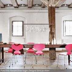Esstisch in renovierter Scheune mit magentafarbenen Designer-Stühlen. Weitere Farbideen findet ihr auf www.roomido.com
