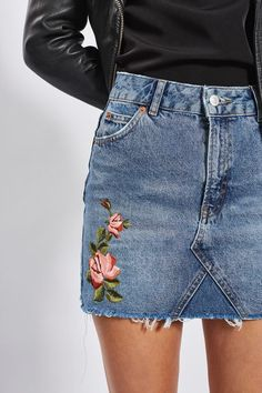 Update the denim skirt in this unique style. In a mid stone blue, it comes in a mini cut, detailed with pretty floral rose embroidery and is finished with a frayed hem. #Topshop