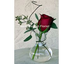 A simple centerpiece designed with a single red rose resting in a sweetheart vase with Seeded Eucalyptus and designer wire.