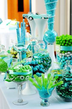 Guests filled bags at a turquoise and lime green hued candy bar offering vintage treats. The colorful candies filled glass vases of various shapes and sizes.