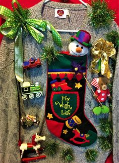 A man's X lg. totally decked out festive sweater with a fun wish list Christmas stocking, a bear, snowman, train, rocking horse and even an airplane on the front side. Green and gold garland balls run down one of the sleeves. The back side has a huge red ornament. Sure to be a hit in this one.