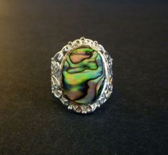 Great looking vintage abalone ring Modena silver 925. The ring consists of a flat oval shaped abalone top surrounded by silver filigree sides. The 925 mark and the initials MO are inscribed on the back.    Size: 8    Condition: Excellent. Minor surface wear on the bottom of the band.