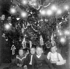 Christmas Day, 1900. Old-time Christmas with candles on the tree. www.christmasgiftsfromgermany.com
