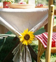 Sunny Tablecloth - For a simple tablecloth, simply fold raw yardage of blue ticking and drape it over your table. At each end of the table, gather the cloth, tie it with twine, and tuck a sunflower into the knot.