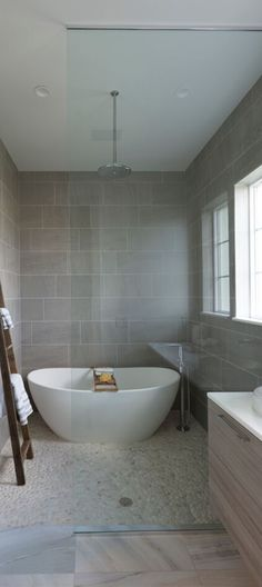 A modern design bathroom has the luxury of a freestanding bathtub along with the comfort of a rainfall shower. Seen in Naples Reserve, a Naples community.