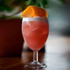 Batida Rosa cocktail: 2 oz Cachaça, 1 oz Pineapple juice, 0.5 oz Lemon juice, 0.5 oz Grenadine, 1 oz Club soda, Garnish: Orange peel