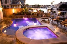 This roman shaped pool includes decorative glass tile at for Pool and spa show usa