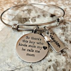 """This engraved personalized Mothers bangle bracelet features a silver colored non tarnishing stainless steel 1"""" pendant that will be custom engraved in our studio with EITHER """"There are these boys...they kinda stole my heart....they call me Mom"""" OR """"So there's this boy....he kinda stole my heart....he calls me Mom""""The 1"""" stainless steel tags will be personalized with your sons' name(s). Includes a silver filled puffy heart charm.Bracelet measures..."""