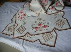 Beautiful needlework in tan and brown with red flowers.