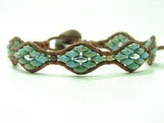 This beautiful Southwest diamond shaped single wrap bracelet is made of 2 1/2 x 5 mm turquoise blue picasso, silver super duo beads. It is woven on a distressed leather cord using a silver metal button for the closure. The bracelet has two sizes that measure at 7 & 8 from the loop to the button and is 1/2 wide. If you need a different size, let me know at check out. It will add 1-3 days to order.