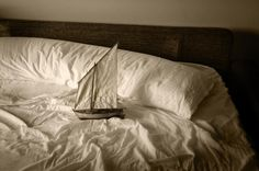 """For his project titled """"Ara Solis"""", Guatemalan photographer Luis González Palma created a series of images representing small models of 15th century sailing boats, symbolically 'crossing the seas' of different sleeping beds. Ideas of migration, intimacy and dreams of the future are brought about in this wonderful series."""