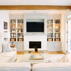 Chic living room features a white linen sectional lined with blue pillows facing a blue striped ottoman as coffee table.