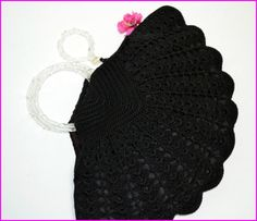 Vintage 1940's Black Crochet Handbag with Lucite Handles & Carved Lucite Pull. $125.00.    This purse really is very special.. I believe this has been crocheted from black cord. The shape is so pretty and the twisted clear lucite circular handles just make the perfect addition to this beauty. What I love the most is the pull cord on the zip closure with the matching twisted lucite handle that has been carved with leaves. It has been lined with a sturdy fabric and has two pockets, one zipped.