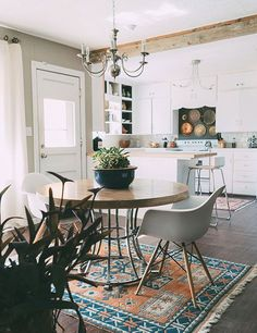 Kitchen Reno Inspiration. Retro inspired kitchen and dining room with round wood table and white boho chairs