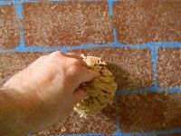 Painting faux brick with a sea sponge and glaze.