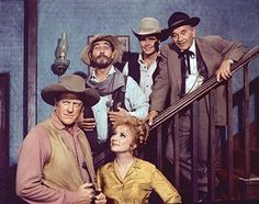 Promotional portrait of the cast of the American television series 'Gunsmoke,' July 23, 1969. Foreground, American actors James Arness (Marshal Matt Dillon) and Amanda Blake (1929 - 1989) (as Kitty Russell); on staircase from left, Ken Curtis (1916 - 1991) (as U.S. Deputy Marshal Festus Haggen), Buck Taylor (Newly O'Brien), and Milburn Stone (1904 - 1980) (as Dr. Galen Adams).