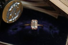 Handmade, Art deco inspired Moissanite engagement ring in 14 karat rose gold by The North Way Studio.