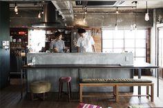 <p>キッチンを囲むテーブルは、組み合わせると大テーブルにできる便利な仕様。たくさん吊るしたエジソン球がレトロ。</p>