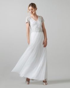A stunning full length wedding gown with a striking fully embellished bodice, sheer cap sleeves and an intricately detailed waistband. The dress comes with an alluring cut out on the upper back, button fastenings at the back neck and a full tulle skirt.