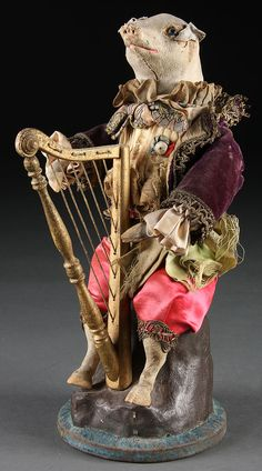 A RARE FRENCH PIG PLAYING HARP AUTOMATON MUSIC BOX, 19TH CENTURY. The leather covered figure of a sitting pig dressed in elaborate clothes on a tree stump playing a gilt wood harp. Clock work key wind mechanism operating a music box with moving arms.