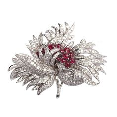 Van Cleef & Arpels Magnificent Diamond Ruby Dahlia Flower Brooch, A magnificent brooch manufactured by Van Cleef & Arpels during the 1950s, representing a a sophistically articulated dahlia flower. The item presents approximately 18cts of brilliant and baguette cut diamonds enriched by 5cts of cabochon rubies in the central element of the brooch. Mounting is in platinum. circa 1950. 1stdibs.com