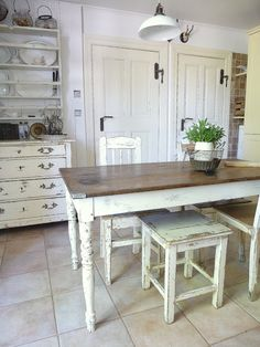 Island with natural top, antique off white legs. With storage shelf underneath and drawers. Large wicker baskets under on shelves.