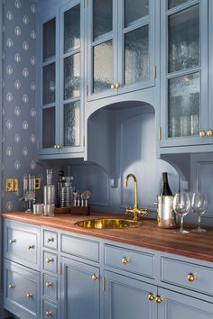 Blue butler's pantry features blue cabinets, upper cabinets accented with seeded glass cabinet doors, adorned with brass knobs paired with wood countertops fitted with a round brass sink and gold vintage style faucet. Blue Kitchen Cabinets, Upper Cabinets, Kitchen Pantry, New Kitchen, Kitchen Decor, Glass Kitchen, Glass Cabinets, China Cabinets, Kitchen Wood