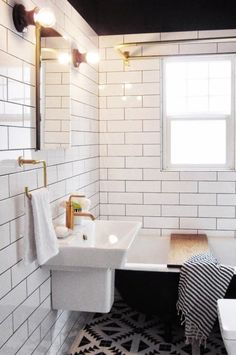 Monochrome bathroom with gold and brass fittings and subway tiles