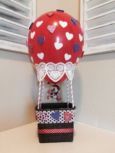 "Hot Air Balloon Valentine's Day Box -  small basket, ribbon, stretchy headband, foam hearts (or other embellishments), paper straws, doilies and balloon. Hot glue paper straws to basket. Double stick tape balloon to straws and cover with doilies (or ribbon). Added the foil heart wire ribbon for the ""fire effect"" on the balloon."