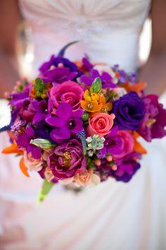 Orange star of Bethlehem, fuschia orchids, purple Lisianthus, blue Veronica, peach Hypericum, orange Lilies, and peach roses.