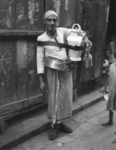 EGYPT - CIRCA 1930s: Egyptian man with large pitcher strapped to chest, on street selling lemonade, Cairo