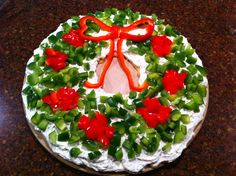 Pampered chef cool veggie pizza shaped like a wreath using green and red bell peppers, cream cheese and crescent rolls.